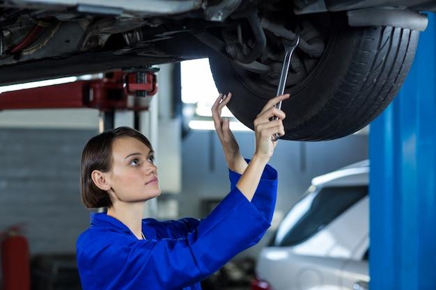 Kobieta mechanik mocowania hamulca tarczowego koła samochodu