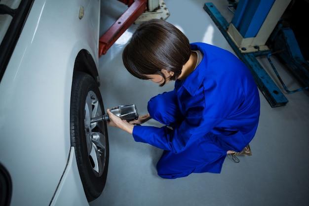 Kobieta mechanik mocowania koła samochodu z kluczem pneumatycznym