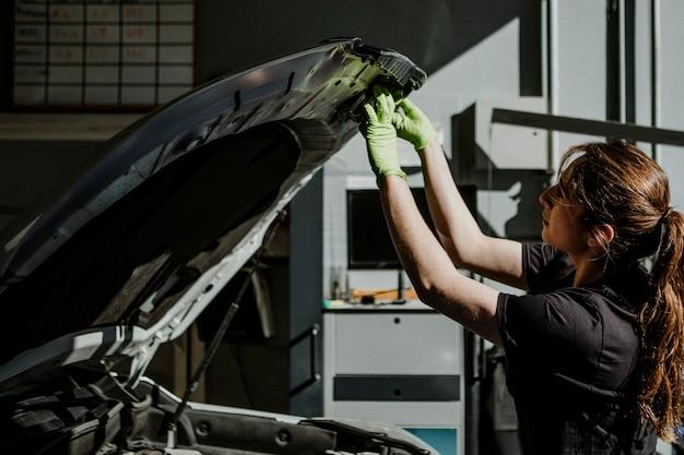 Kobieta mechanik otwierająca maskę samochodu