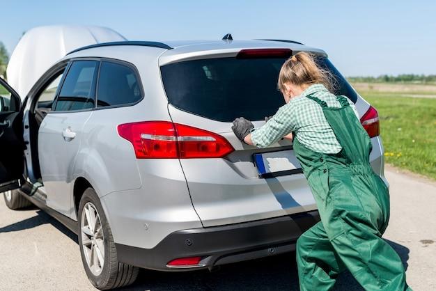 Kobieta mechanik pcha uszkodzony samochód na poboczu drogi