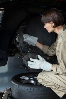 Kobieta mechanik samochodowy naprawa hamulców