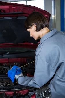 Kobieta mechanik sprawdzania poziomu oleju w silniku samochodowym