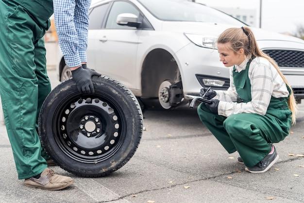 Kobieta mechanik sprawdzanie koła zapasowego w pobliżu samochodu