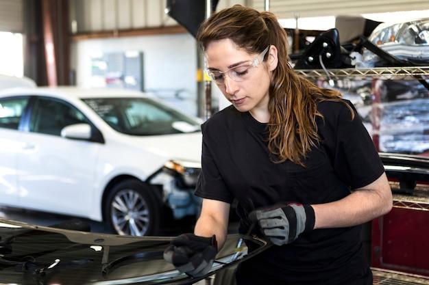 Kobieta mechanik wyciągająca uszczelkę pogodową pojazdu