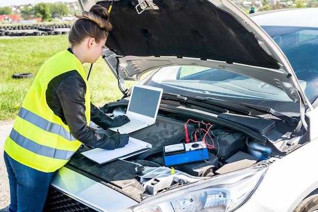 Kobieta mechanik wykonująca diagnostykę zepsutego samochodu