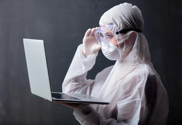 Kobieta medic noszenie odzieży ochronnej przed wirusem z komputera przenośnego