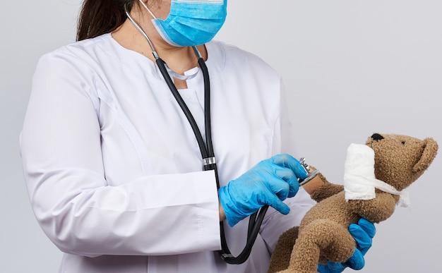 Kobieta medyk trzyma brązowego misia z łapą obandażowaną w biały bandaż
