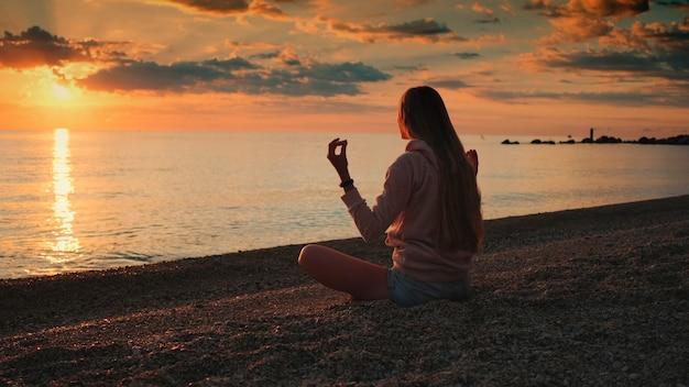 Kobieta medytacja nad morzem przed zachodem słońca