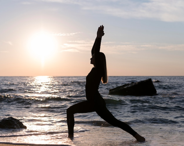 Kobieta, medytując na plaży o zachodzie słońca