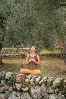 Kobieta medytująca i oddychająca w parku