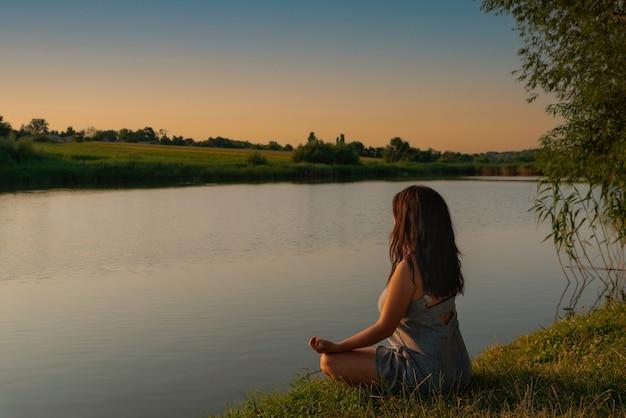 Kobieta medytująca w pozycji lotosu podczas zachodu słońca joga medytacja spokój relaks na łonie natury