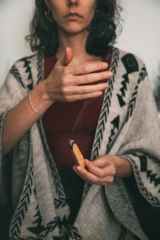 Kobieta medytująca z dymem palo santo ubrana w ręcznie wykonane poncho medytacjapionowa