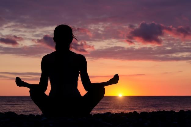 Kobieta medytuje na plaży w pozycji lotosu. sylwetka, zachód słońca