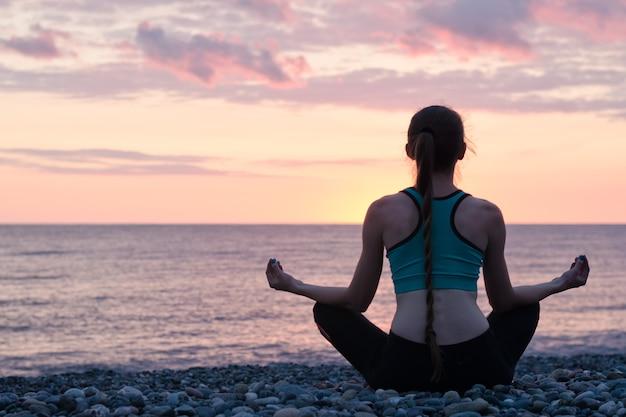 Kobieta medytuje na plaży w pozycji lotosu. zachód słońca. widok z tyłu