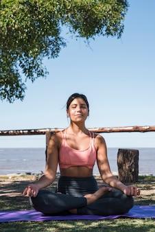 Kobieta medytuje przy plażą