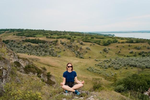 Kobieta medytuje relaksujący samotnie. podróżuj zdrowym stylem życia z pięknym krajobrazem