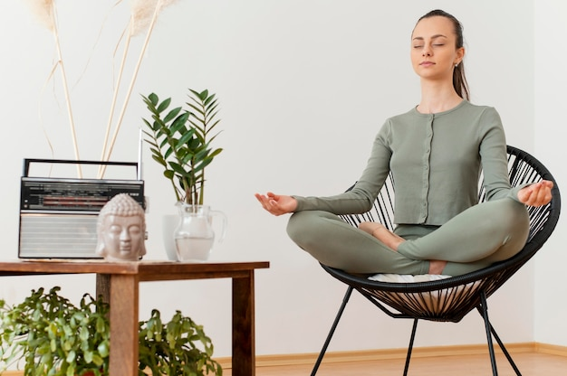 Kobieta medytuje w domu na krześle