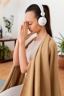 Kobieta medytuje w domu ze słuchawkami