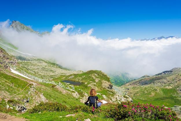 Kobieta medytuje w naturalnym środowisku na górach.