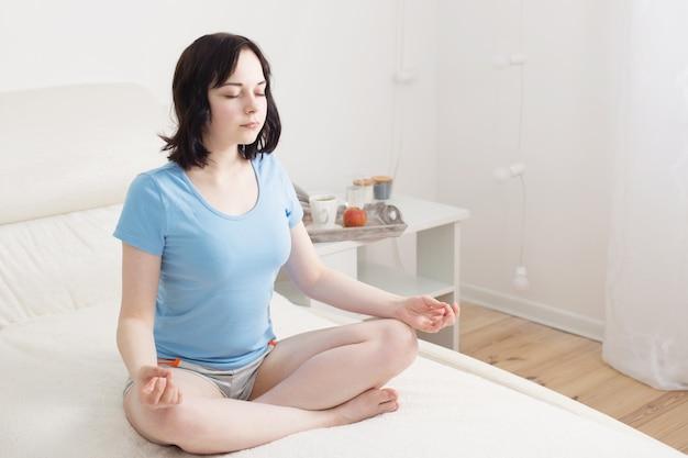 Kobieta medytuje w sypialni