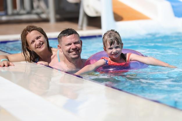 Kobieta, mężczyzna i córka uśmiechają się razem. rodzina pływać w basenie w słońcu.