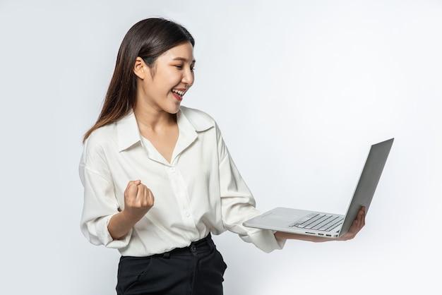 Kobieta miała na sobie białą koszulę i ciemne spodnie, trzymała laptopa i udawała radość