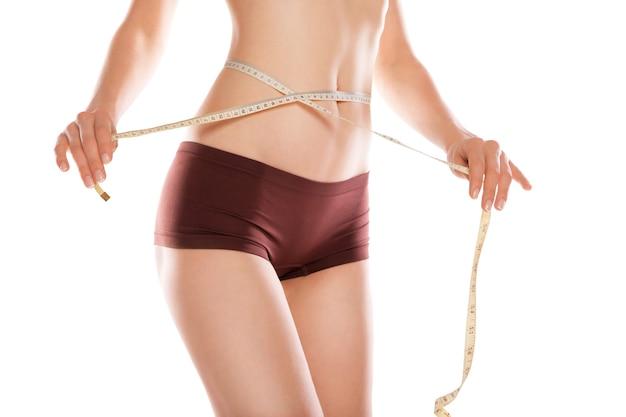 Kobieta mierząca talię na białym tle