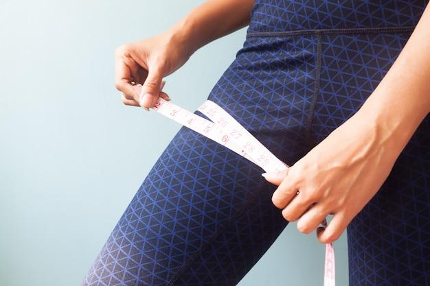 Kobieta mierzy jej nogi, ciężar stratę lub zdrowego pojęcie