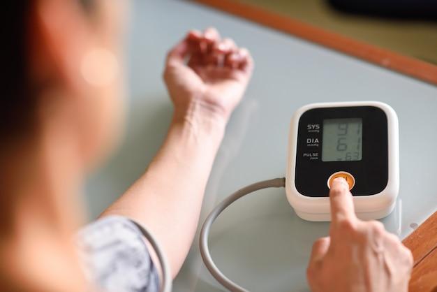 Kobieta mierzy jej własne ciśnienie krwi w domu.