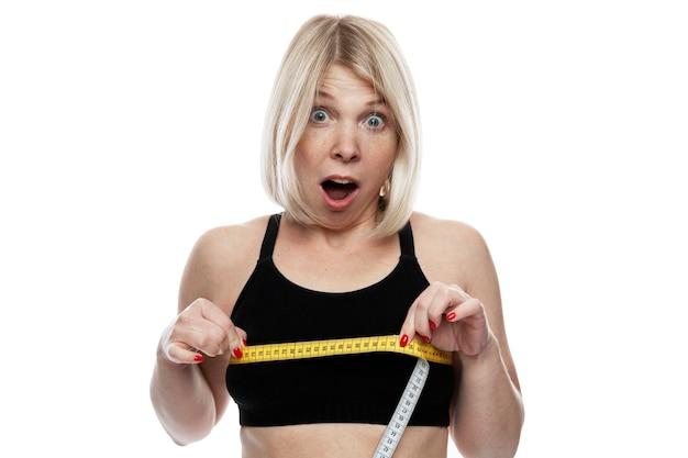 Kobieta mierzy objętość swoich piersi. zaskoczona blondynka w czarnym staniku.