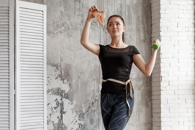 Kobieta mierzy obwód talii, trzyma hantle, patrzy na kawałek pizzy