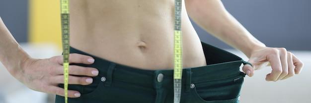 Kobieta mierzy swoje stare dżinsy i odnotowuje efekt utraty wagi