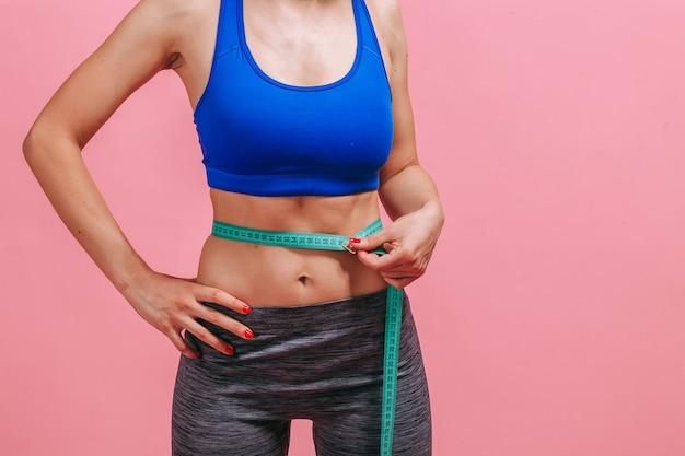 Kobieta mierzy talię na zbliżeniu różowej ściany