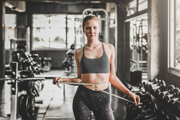 Kobieta mierzy talię w siłowni fitness