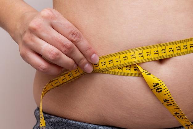 Kobieta mierzy talię żółtą taśmą. koncepcja fitness diety.