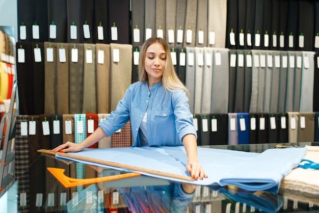 Kobieta mierzy tkaninę w sklepie tekstylnym. półka z materiałem do szycia
