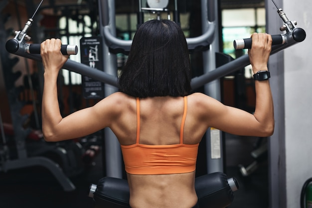 Kobieta mięśni kulturysta ćwiczeń. kobieta lekkoatletycznego za pomocą maszyny do pompowania mięśni pleców w siłowni, widok z tyłu