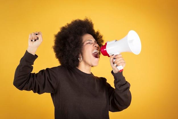 Kobieta mieszanej rasy, polityczna syndykalistyczna feministka, oddana równości, wrzeszczy w megafon,