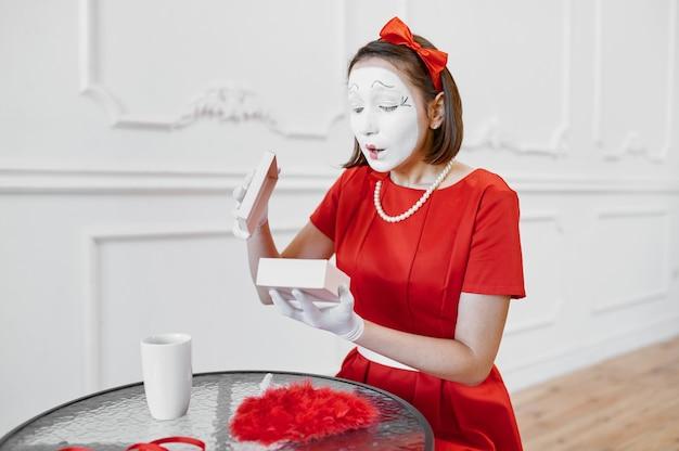 Kobieta mim w czerwonym stroju, scena z prezentem