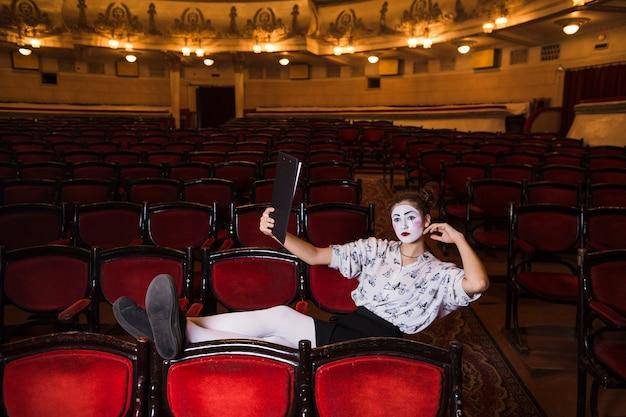 Kobieta mime z manuskryptem siedzi na krześle