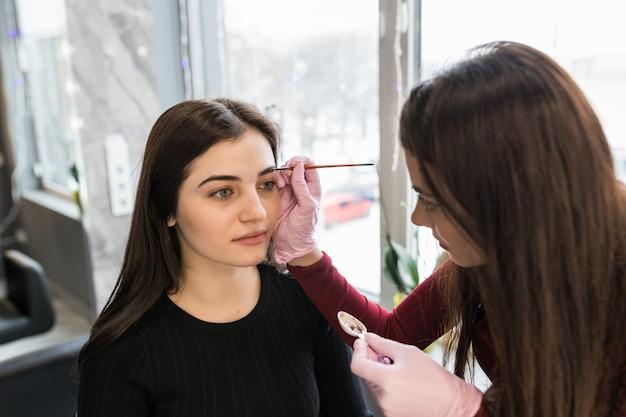Kobieta-mistrz nakłada farbę do brwi podczas procedury makijażu