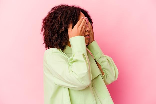 Kobieta młody african american rasy mieszanej boi się obejmujących oczy rękami.