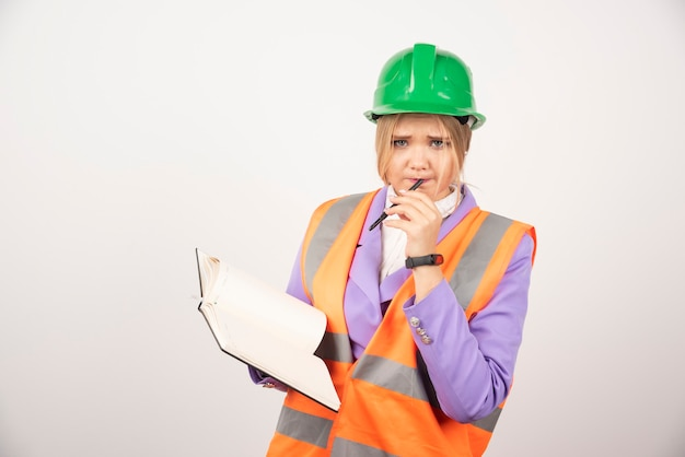 Kobieta młody architekt w kasku z tabletem na białym tle.