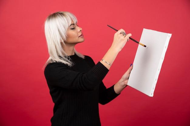 Kobieta młody artysta rysunek na płótnie na czerwonej ścianie.