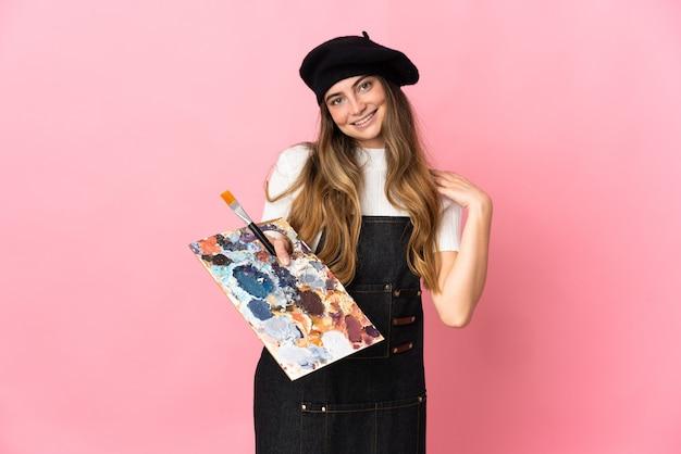 Kobieta młody artysta trzyma paletę na białym tle na różowy śmiech