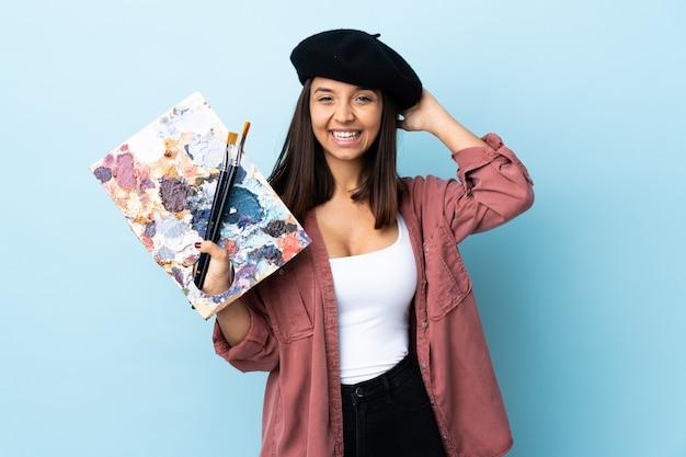 Kobieta młody artysta trzyma paletę na białym tle niebieski śmiech.