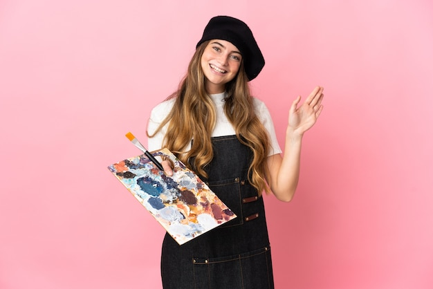 Kobieta młody artysta trzyma paletę na różowo salutowanie ręką z happy wypowiedzi