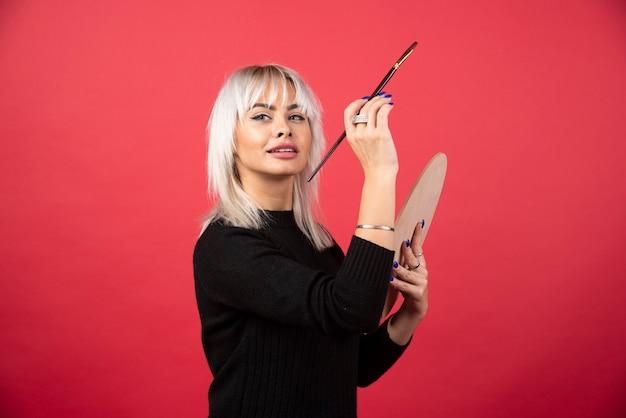 Kobieta młody artysta trzymając dostaw sztuki na czerwonej ścianie.