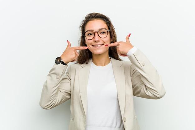 Kobieta młody biznes europejski uśmiecha się, wskazując palcami na usta.