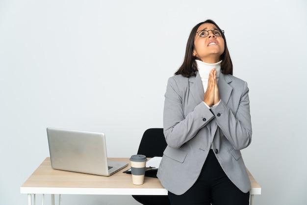 Kobieta młody biznes łacińskiej pracująca w biurze na białym tle na białej ścianie trzyma dłoń razem.